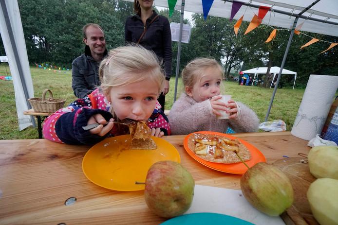 Feline en Isabel Kops eten pannenkoeken met appels en appelsap op het oogstfeest in Malden.