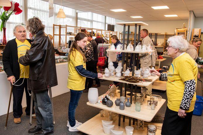 Open dag bij kringloopwinkel de Vince aan de Koele Mei in Breda. Vrijwilligers in alle leeftijden, herkenbaar aan de gele shirts, helpen de klanten.