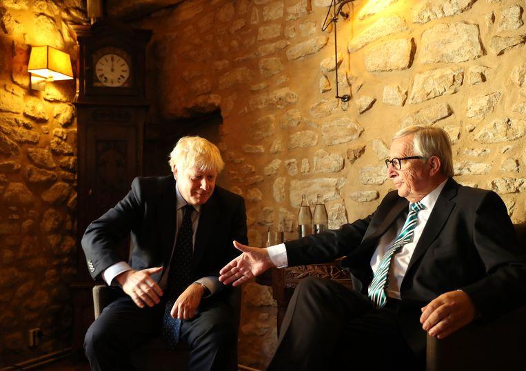 Jean-Claude Juncker (r.) reikt maandag zijn hand uit naar Boris Johnson, voorafgaand aan hun lunch in een restaurant in Luxemburg. Beeld AP