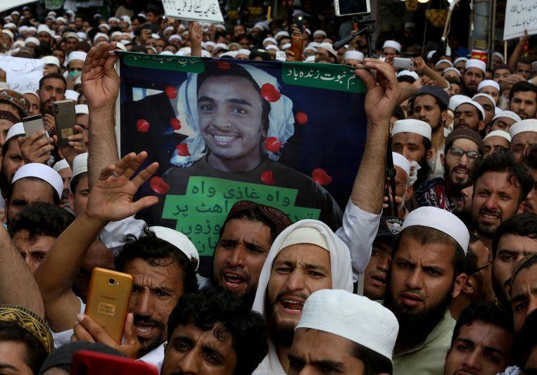 Aanhangers van een religieuze groepering houden een bord omhoog met daarop de foto van de tiener die Tahir Naseem vermoorde. Beeld AP