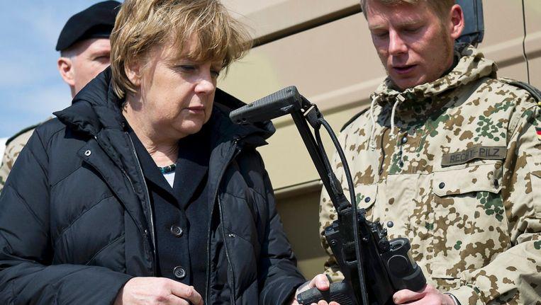 Angela Merkel inspecteert tijdens een reis naar Afghanistan in 2012 een Heckler & Koch MP7 machinegeweer. Een ander wapen, de HK G36, heeft problemen in warme klimaten. Beeld reuters