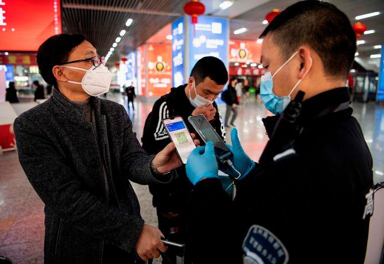 Een Chinese treinpassagier toont zijn telefoon: groen, dat betekent dat hij een laag risico is. Beeld AFP