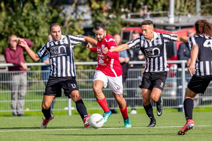 Sportlust'46-aanvaller Abdelmalek El Hasnaoui wordt vastgehouden door Ali Gencalioglu en doelpuntenmaker Sharif Lopez Garrido van Achilles'29.