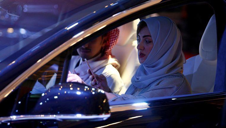 Een vrouw met hoofddoek zit achter het stuur in Saoedi-Arabië. Beeld null