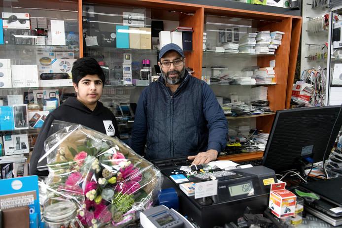De 15-jarige Toheed Malik (l) en vader Asif Malik werden woensdagmiddag overvallen in hun telefoonzaak in Nieuwleusen. Buren brachten bloemen om het leed wat te verzachten.