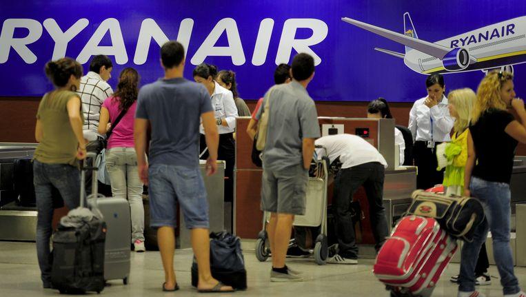 Passagiers checken in bij de Ryanairbalie op de luchthaven van Barcelona.