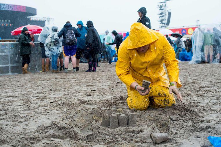 Een man gehuld in gele regenjas speelt in het zand op de eerste, regenachtige dag van Rock Werchter. Beeld afp