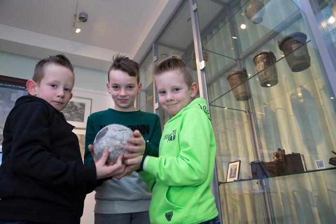 Sem, Milan en Gijs (van links naar rechts) met de middeleeuwse kanonskogel die ze hebben gevonden in Doetinchem.