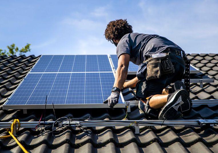 Een installateur plaatst zonnepanelen op het dak van een woonhuis.  Beeld ANP