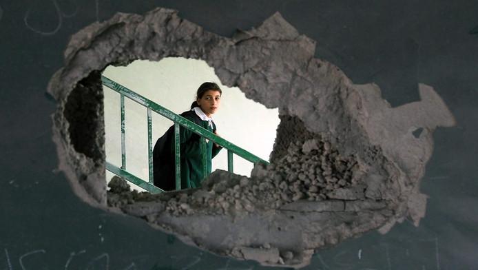 Een palestijns schoolmeisje kijkt door een gat in de muur van haar in puin geschoten school.