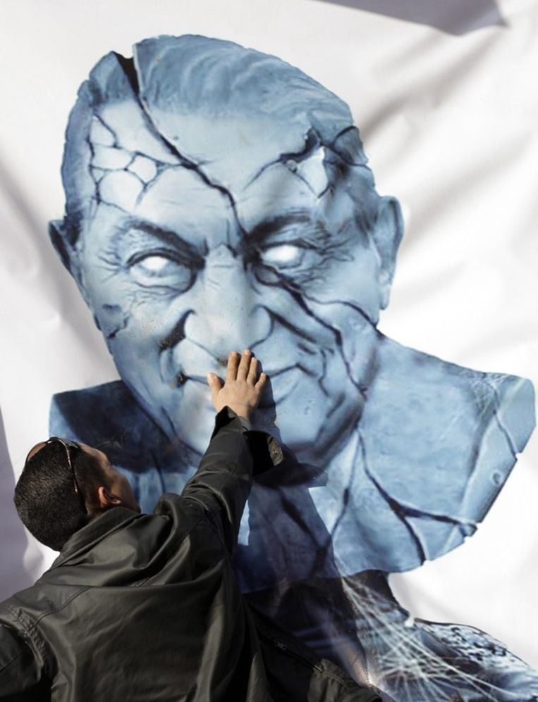 Een spandoek met een afbeelding van Mubarak op het Tahrirplein in Caïro. Beeld epa