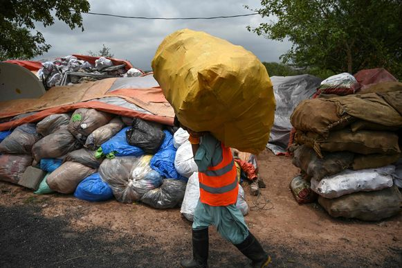 In this picture taken on July 16, 2019, a municipal worker carries a bag of recycling items at a site in Islamabad. - From the once pristine rivers of Hindu Kush to the slums of Islamabad, Pakistan is being smothered by plastic due to a lack of public awareness, government inertia, and poor waste management. (Photo by AAMIR QURESHI / AFP) / TO GO WITH Pakistan-environment-plastic,FEATURE by Joris Fioriti