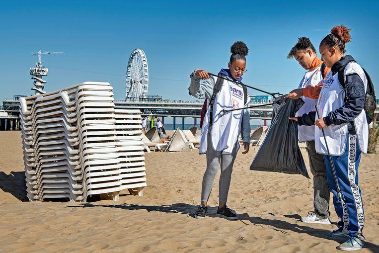Deelnemers aan de actie Swim Sea van het WNF helpen zaterdag bij het schoonmaken van het strand van Scheveningen .  Beeld Foto Guus Dubbelman / de Volkskrant