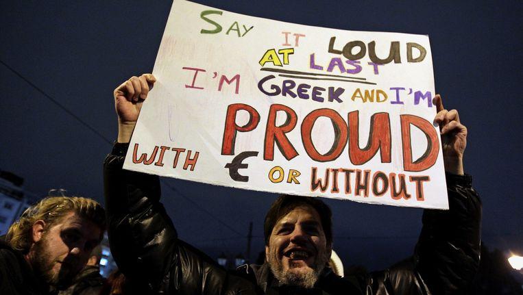 Archieffoto van een protest in Athene waarbij een demonstrant een bord omhoog houdt. 'Ik zeg het eindelijk hardop. Ik ben Griek en trots met euro of zonder.' Beeld epa