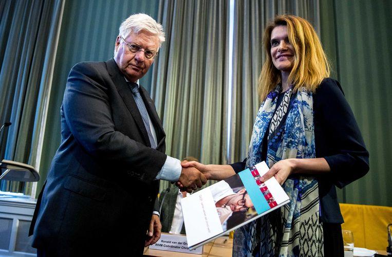 Voorzitter Ruud Vreeman van de Paritaire Commissie overhandigt het rapport aan staatssecretaris Barbara Visser van Defensie (VVD).  Beeld ANP