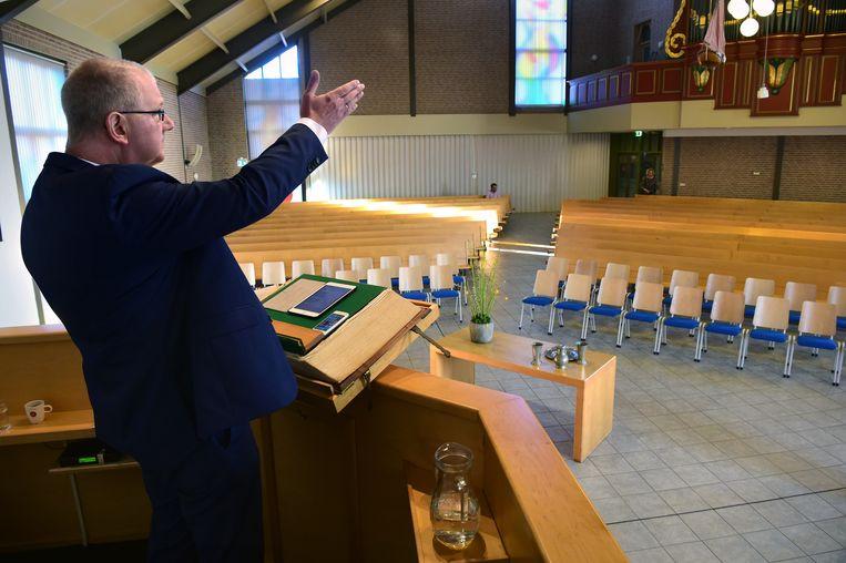 Dominee Arend-Jan de Boer van de Rehobothkerk in Urk neemt zondagochtend de dienst op die de leden van de gereformeerde kerk even later thuis kunnen beluisteren. Beeld Marcel van den Bergh