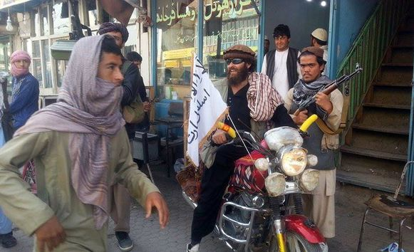 Een talibanstrijder rijdt door Kunduz op een motor met een talibanvlag.