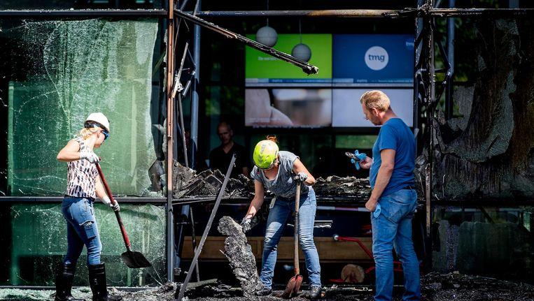Er werd dinsdagochtend uitvoerig puin geruimd voor de deur van het TMG-gebouw op de Basisweg. Beeld anp