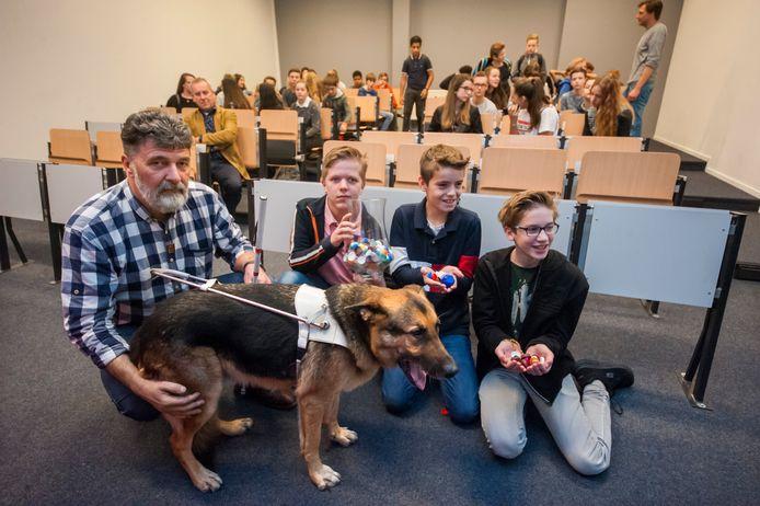 Hans Ebbing met zijn geleidehond Koray en de leerlingen (vlnr) Teun, Sven en Marco  van klas 2BA van het Baanderherencollege in Boxtel met de doppen die de klas al heeft ingezameld voor de actie.