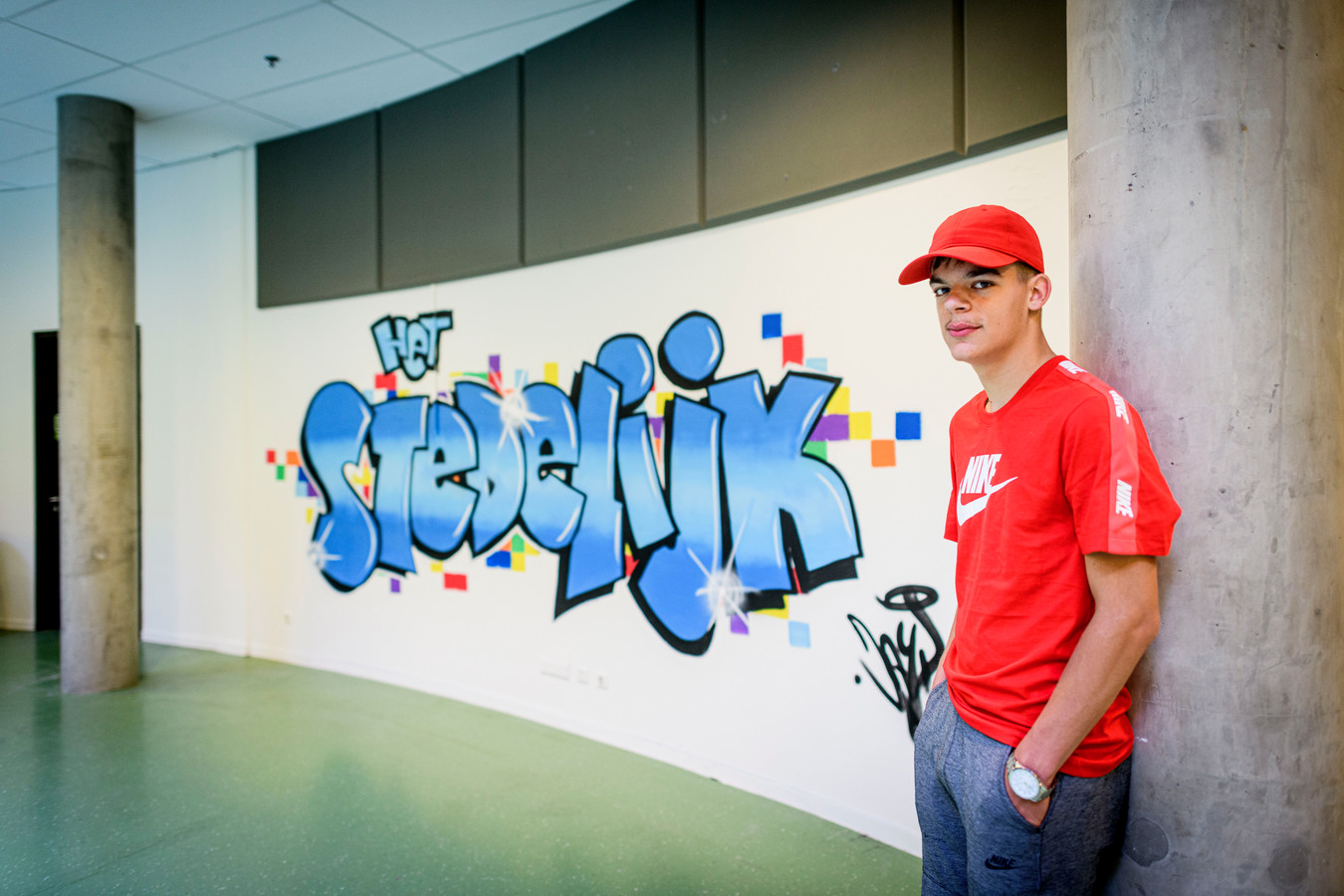 Jayden van Stuivenberg (17) heeft een mooi graffitikunstwerk gemaakt in zijn eigen school in Enschede aan de Wethouder Beverstraat.  FOTO: Emiel Muijderman EVM20200625