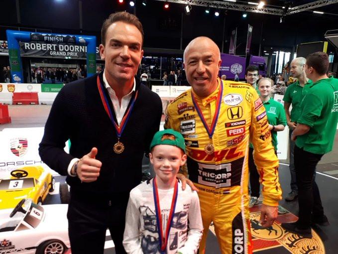 Autocoureurs Robert Doornbos (l) en Tom Coronel met een deelnemertje aan de trapauto-wedstrijd.