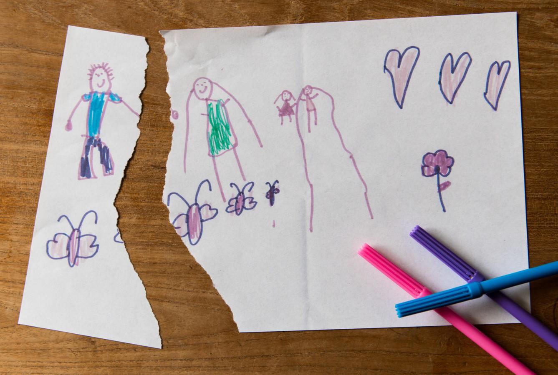 Foto ter illustratie. Een door midden gescheurde kindertekening van een familie.