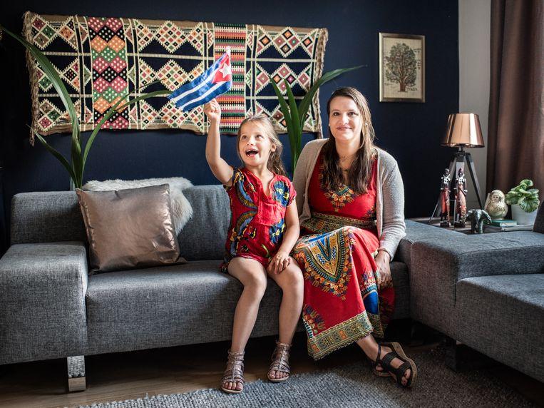 Kelly Litjens met haar dochter Nikki in hun woonkamer vol souvenirs uit verre landen. Beeld Simons Lenskens