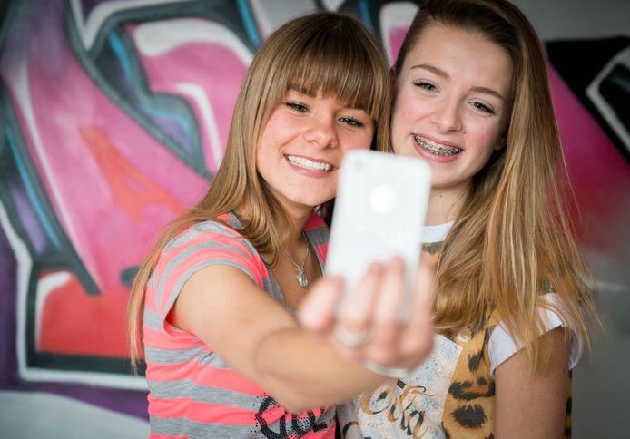 Twee meisjes met hun smartphone.