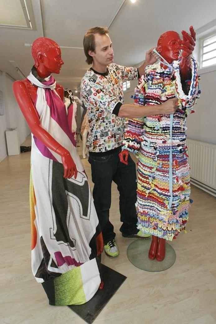 De uit Vorden afkomstige mode-ontwerper Antoine Peters exposeert momenteel in de galerie van de bibliotheek in Vorden. De jurk van stroken joggingstof waaraan hij de laatste hand legt is door zijn moeder gebreid met aangepunte bezemstelen. Ook de trui die hij draagt is een eigen ontwerp en dus een unicum. foto Jan Houwers
