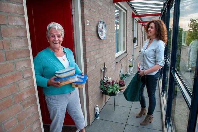 Daniëlle Kivits (r), aangesloten bij Stichting Thuisgekookt, bezorgt de door haar gemaakte maaltijden bij haar buurtgenoot Beppy Stoks in Den Bosch. Het buurthuis waar Stoks vaak at, is dicht vanwege de coronamaatregelen.