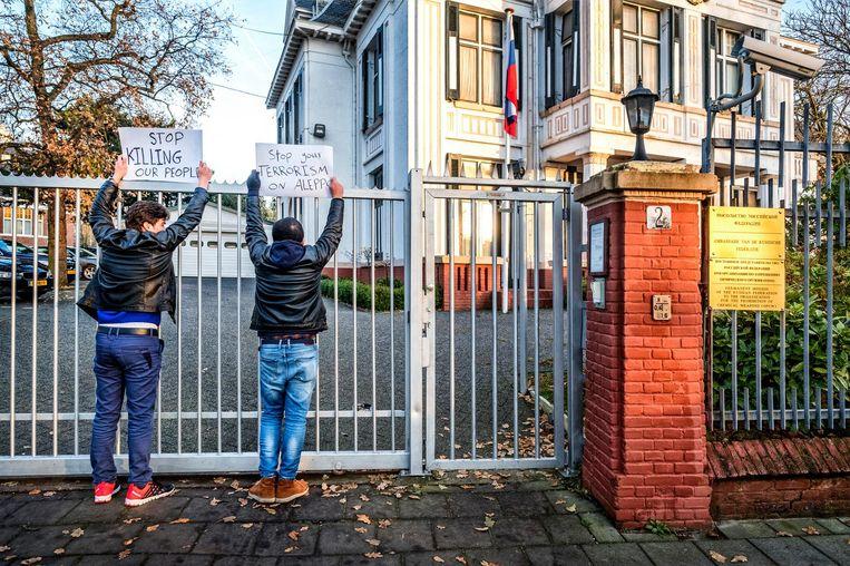 Abdel-Qader Zalkha en Fouad Hallak bij de Russische ambassade in Den Haag. De twee Syrische vluchtelingen zijn opgepakt nadat ze zich hadden vastgeketend aan een poort. Beeld Raymond Rutting/de Volkskrant