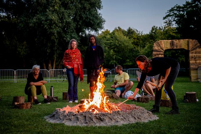 Mensen ontmoeten elkaar bij het kampvuur. Er werden ook liedjes gezongen.