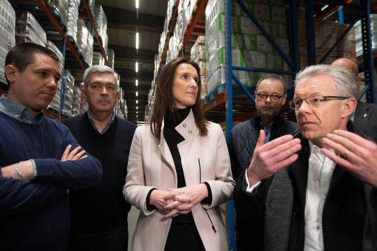 De Belgische premier Sophie Wilmès (midden) tijdens een bezoek aan een opslagcentrum van de supermarktketen Colruyt.  Beeld BELGA
