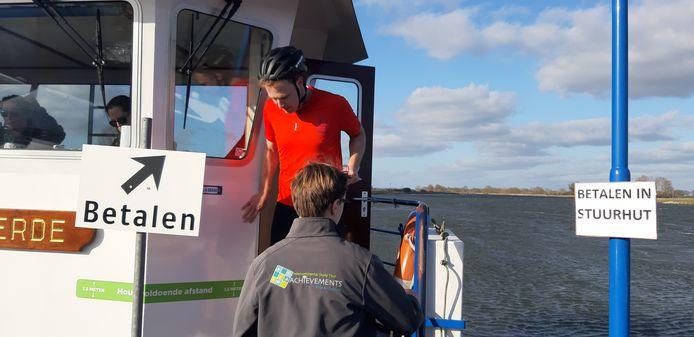 Coronacrisis, dat betekent dat personeel van de Wijhese pont over de IJssel zich niet op het veer vertoont. Binnenblijven in de stuurhut, waar een tijdelijk betaalloket is ingericht en passagiers uit de auto moeten stappen