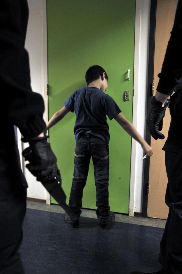 Uitgeprocedeerde Iraakse asielzoekers worden in de nacht per charter uitgezet naar Irak. Een jongetje wordt gefouilleerd door de Koninklijke Marechaussee. Beeld Joost van den Broek