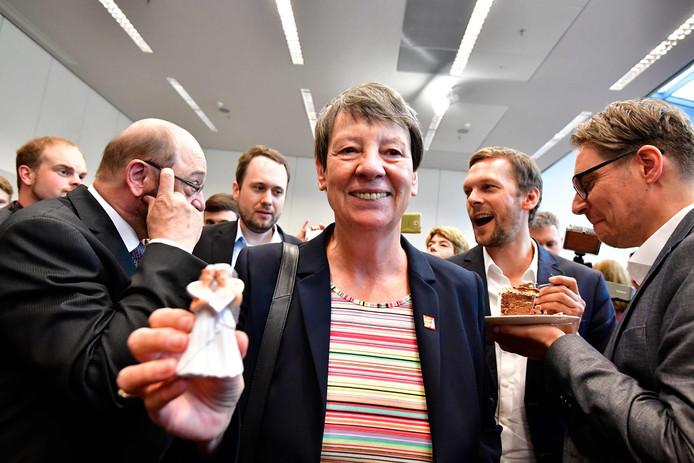 De Duitse minister van Milieu Barbara Hendricks houdt een figuurtje van twee bruiden in haar handen vlak tijdens de viering van de openstelling van het homohuwelijk in het Duitse parlement.