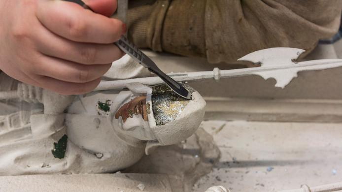 Het verwijderen van de witte verf van de kruiswegstatiën is een nauwkeurig werk. De studenten van Vakschool Nimeto uit Utrecht gebruiken daarbij scalpelmesjes.