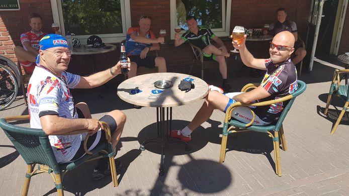 Vader en zoon Hairwassers uit Den Dungen en de rest van de fietsgroep proosten op hun eerste biertje op het terras.
