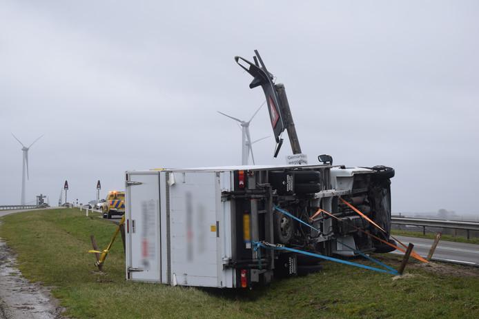 Een bakwagen werd door de harde wind omver geblazen en kwam op zijn kant terecht op de N257 in Bruinisse. De vrachtwagen kan momenteel niet weggesleept worden omdat het te hard waait. Om te voorkomen dat de bakwagen nog verder van zijn plek waait is het voertuig vast gezet met spanbanden.