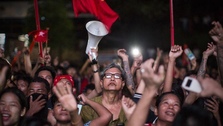 Aanhangers van de NLD, de partij van de Birmese oppositieleidster en Nobelprijswinnares Aung San Suu Kyi, reageren op voorlopige uitslagen. Beeld Julius Schrank