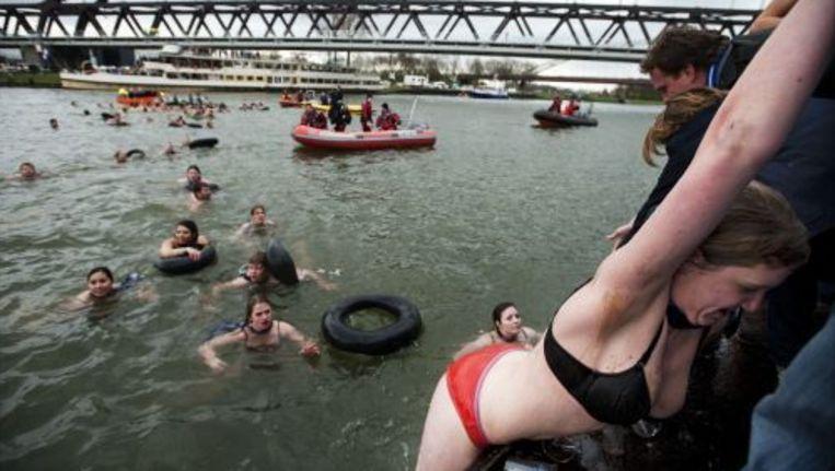 Een studente van de Rotterdamse studentenroeivereniging Skadi wordt zondag uit het Amsterdam-Rijnkanaal gehesen tijdens de 127e Varsity. De studenten zwommen traditioneel hun winnende boot in de klasse 'Oude Vier' tegemoet in het ijskoude water van het kanaal. Foto ANP Beeld