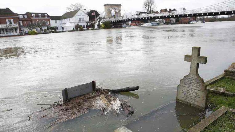 Een kerkhof is overstroomd nadat de Theems een recordpeil heeft bereikt Beeld reuters