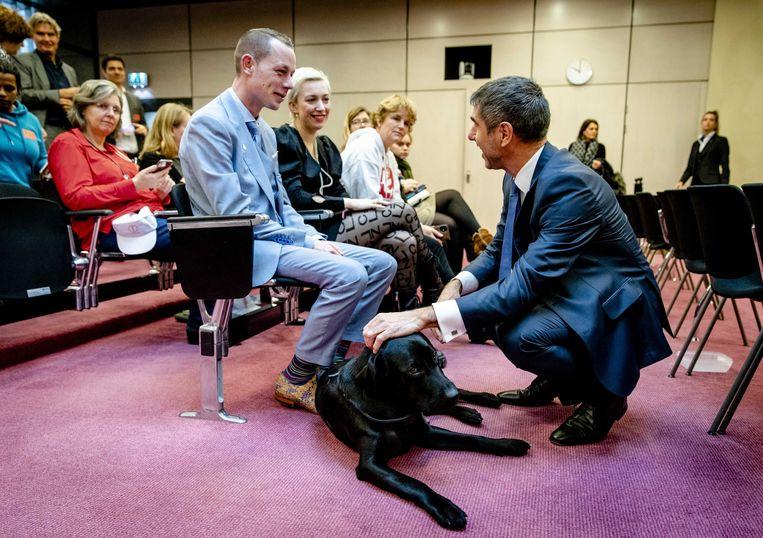 Paul Blokhuis, staatssecretaris van Volksgezondheid, Welzijn en Sport, begroet hond Bobby van Charlotte Bouwman voorafgaand aan een algemeen overleg in de Tweede Kamer over de geestelijke gezondheidszorg. Beeld ANP