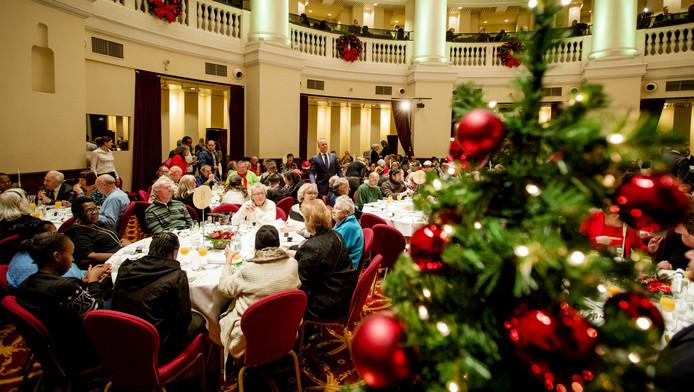 Daklozen en medewerkers van het Leger des Heils zitten samen aan een kerstdiner van het Leger des Heils.