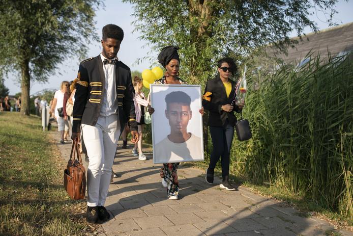 Vrienden en bekenden lopen met een portret van Orlando Boldewijn tijdens een stille tocht ter nagedachtenis aan de 17 jarige jongen die in februari dood werd gevonden.