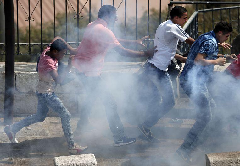 Palestijnen zoeken beschutting voor de traangasgranaten van Israëlische troepen tijdens gevechten rond de al-Aqsa-moskee.