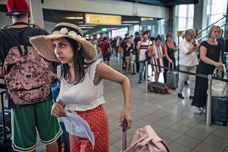 Balende reizigers op Schiphol. Door een storing in de kerosinetoevoer afgelopen zomer konden veel vluchten niet vertrekken of met veel vertraging.  Beeld null