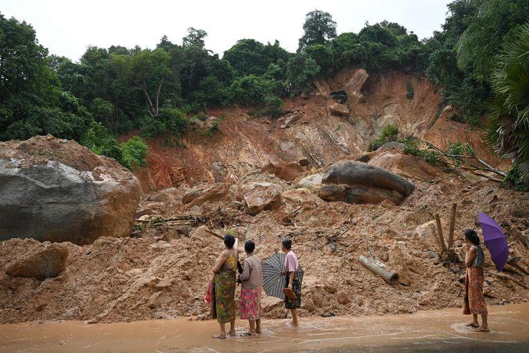 Bewoners kijken naar de ravage die de aardverschuiving aanrichtte.