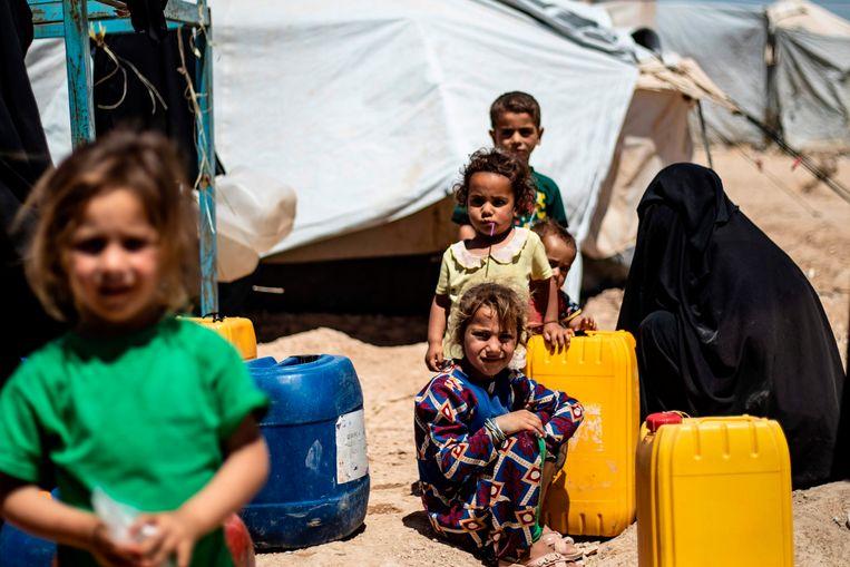 Kinderen staan in een Syrisch vluchtelingenkamp in de rij voor water.  Beeld AFP