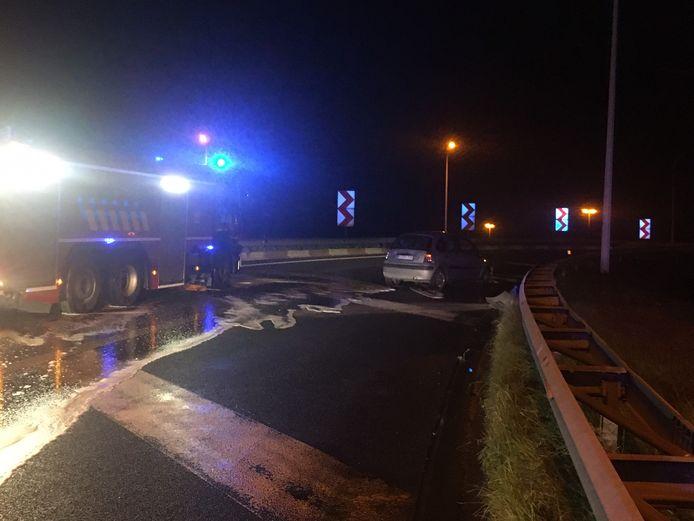 De brandweer spoot de rijweg opnieuw proper na het ongeval. Rechts de slippende wagen.
